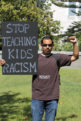 Hispanic_man_with_words_on_a_poster_stop_teaching_kids_racism